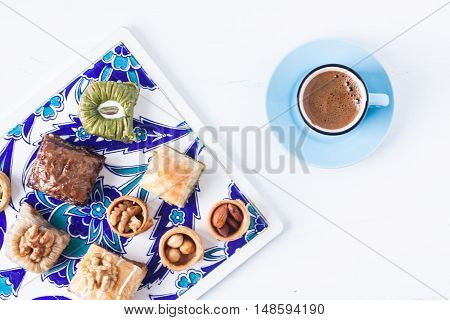 Turkish coffee and assorted baklava desserts on a white background
