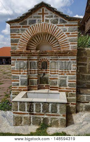 Giginski monastery, Bulgaria - June 25, 2016:  View of inner  part yard with  spring water fountain in restored Montenegrin or Giginski monastery  St. St. Cosmas and Damian, mountain  Kitka, Breznik, Pernik region, Bulgaria. Visit in the place circa June