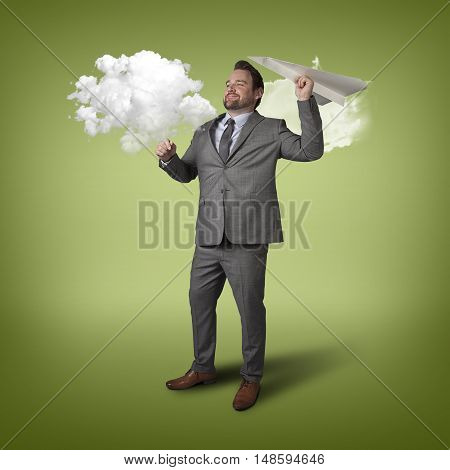 Businessman throwing paper plane with cloud indoor