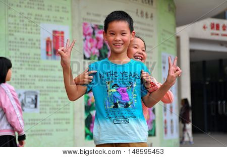 Pengzhou China - October6 2013: Two smiling Chinese children flash the