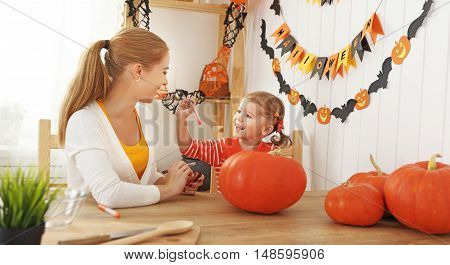 family mother and child daughter are preparing for Halloween carve a pumpkin and decorate the house