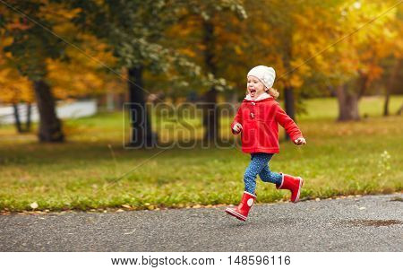 happy child girl running in the nature in autumn after rain