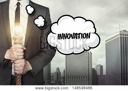 Innovation text on speech bubble with businessman holding lamp