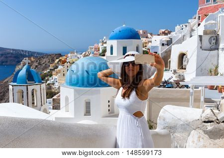 Woman with white hat and white dress is taking selfies in Oia, Santorini, Greece