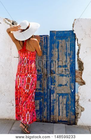 Woman in red dress looking over an old blue vintage door