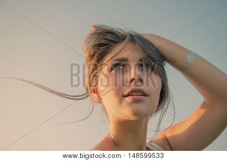 portrait of a teenage girl holding hair with her hand on the background of the sky