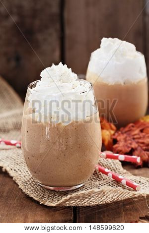 Pumpkin Smoothies with whipped cream against a rustic background. Shallow depth of field with selective focus on dessert in foreground.