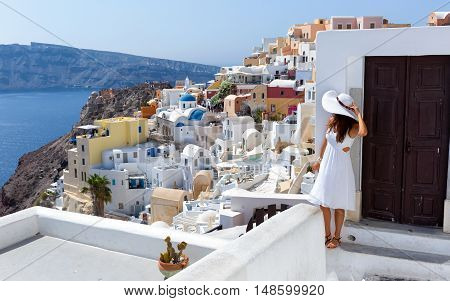 Woman in white dress is watching over the village of Oia, Santorini
