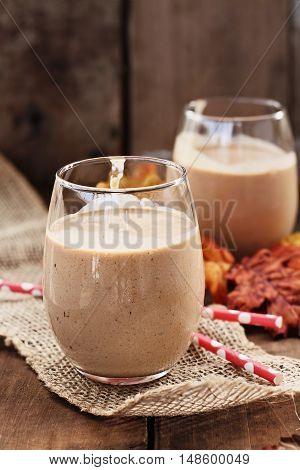 Pumpkin smoothies against a rustic background. Shallow depth of field with selective focus on dessert in foreground.