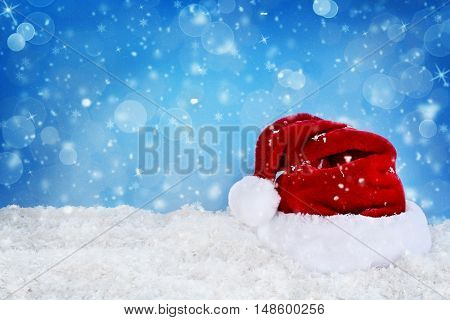 Santa hat decoration for Christmas on snow with a blue background. Shallow depth of field.