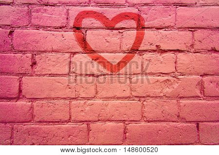 On a brick wall painted a small heart. background. Space blank