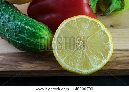 cucumber, tomato, lemon, patison, pepper, garlic, onion on a black background