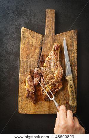 Man spiking a seared dry aged rib eye steak with a fork