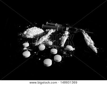 Pills, cocaine drug powder lines and injections on black background in black and white colors