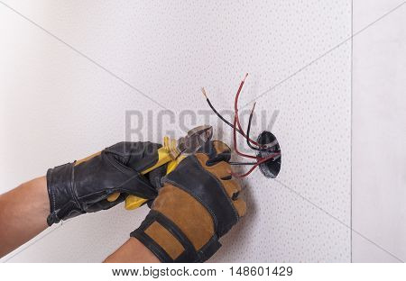 Electrician installs lighting switch in the wall