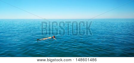 Woman in bikini lying on water at tropical beach. Complete relaxation.