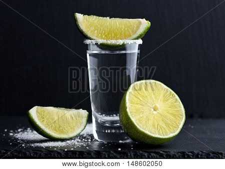 Tequila silver shot with lime slices and salt on stone board