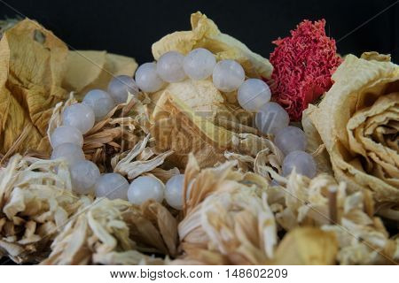 agate bracelet lying on a yellow rose, black background