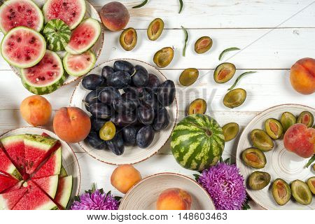 Colorful fruit set of purple red and orange fruit background in bowls. Plum peaches watermelon sliced above white rustic tabletop.