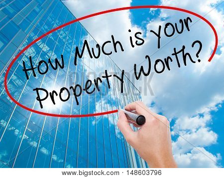 Man Hand Writing How Much Is Your Property Worth? With Black Marker On Visual Screen