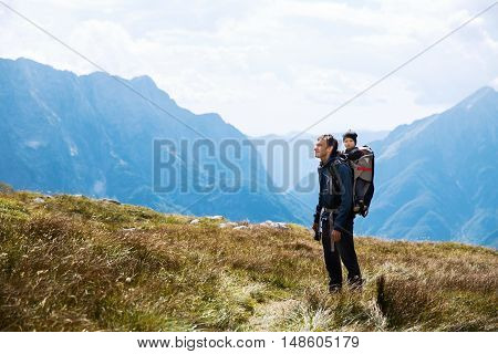 Father hiking with child in carrier backback on the background of mountains. Family on trekking day in the mountains. Mangart Julian Alps National Park Slovenia Europe. Travel Lifestyle Concept.