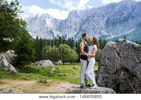 Couple Of Travelers On The Lago Di Fusine Lake With Mangart Mountains In The Background. Udine, Ital