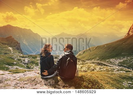 Couple of travelers (hikers) on top of a mountain enjoying valley view. Mangart is a mountain in the Julian Alps, located between Italy and Slovenia. Travel, Holidays, Freedom and Lifestyle Concept. Photo toning warm colors