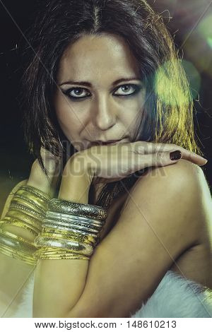 Elegant fashionable woman with silver jewelry over sun flare