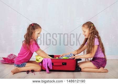 Two girls collect a suitcase on a journey