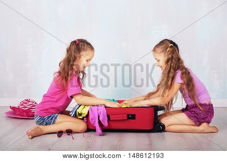 children, two girls, gather clothes in a suitcase