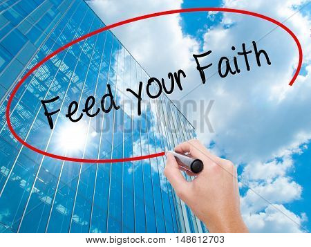 Man Hand Writing Feed Your Faith With Black Marker On Visual Screen