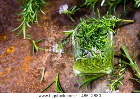 Rosemary oil. Rosemary essential oil jar glass bottle and branches of plant rosemary with flowers on rustic background.
