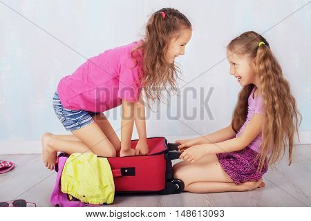 children play and laugh with a suitcase