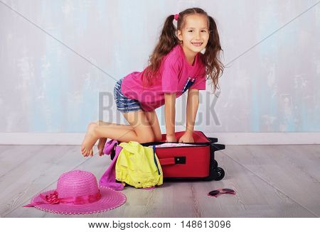 child in shorts and a pink T-shirt going on vacation