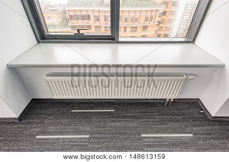White radiator in the office at rainy day time.
