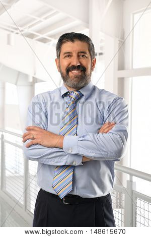 Senior Hispanic businessman smiling with arms crossed inside office building