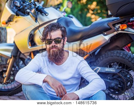 Attractive man bearded hipster biker in sunglasses sits on sidewalk near motorcycle on sunny summer day