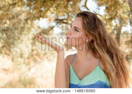 Pretty blonde girl throwing a kiss on a sunny day