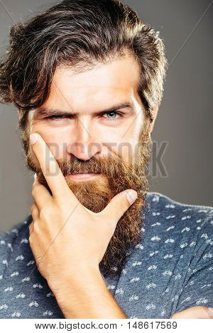 Handsome man hipster with long beard keeps chin with hand on grey background