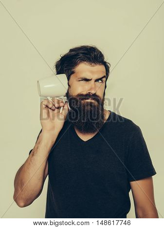 handsome bearded man with stylish hair beard and mustache on surprised face in shirt holding white cup or mug with good morning text drinking tea or coffee in studio on light background