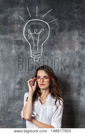 Young Smart Woman In Eyeglasses With Idea Symbol Bulb