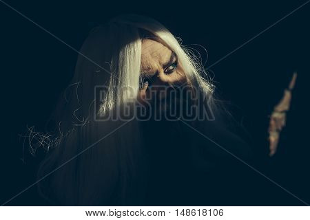 Druid old man face with wrinkles long silver beard and hair with bright light on dark background