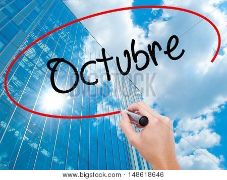 """Man Hand Writing """"octubre"""" (in Spanish: October) With Black Marker On Visual Screen"""