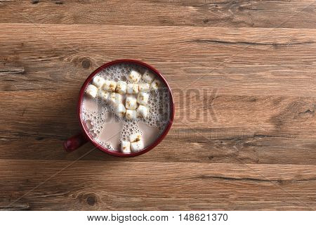 Top view of a single mug of hot cocoa with marshmallows on a rustic wood table.