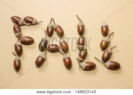 Fall spelled in acorns on beige background