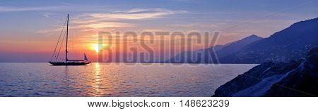 Panoramic view of Sailing at violet sunset with mountains