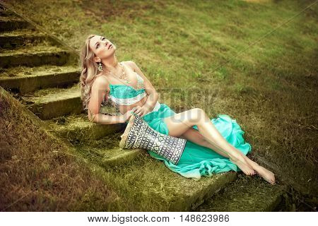 beautiful white woman in a dance costume is lying on a vintage ladder with darbukas. Darbuka an ancient percussion instrument