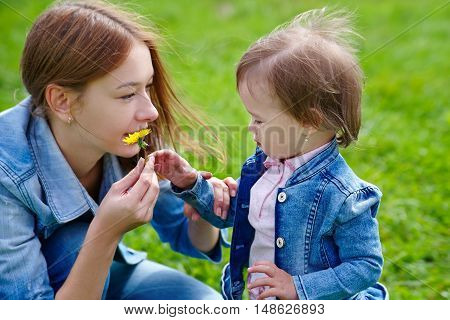 Beautiful young mother and daughter walking outdoors in park grass background summer