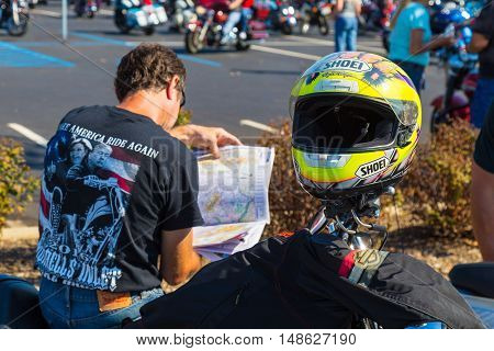 York PA - September 23 2016: A motorcyclist at the annual Harley-Davidson Factory Open House checks a map for his next destination.