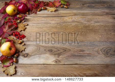 Border of apples acorns berries and fall leaves on the old wooden background. Thanksgiving background with seasonal berries and fruits. Abundant harvest concept.